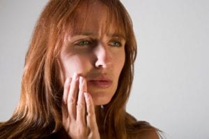 woman placing hand on face indicating toothache