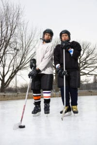 image of two people in hockey gear on ice
