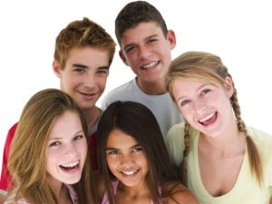 group of five teens smiling