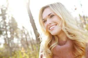woman smiling with the sun shining behind her