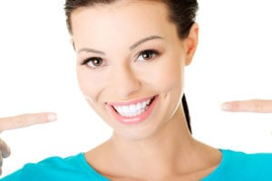 woman smiling and pointing to white smile